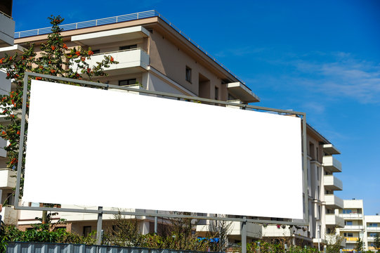 Blank white advertising billboard in front of the building