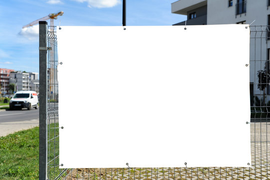 Blank white banner for advertisement on the fence. Residential area on a sunny summer day.
