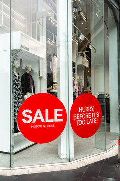Red Sale Sign Sticker on the outside of Fashion Store Windows