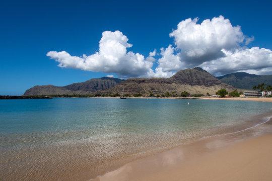 Makaha beach with mountains and blue cloudy sky
