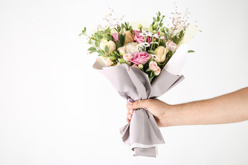 Female hand holding beautiful flower bouquet on white background Fotobehang