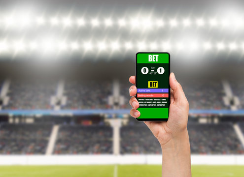 man using a mobile phone shows a betting application with live results and updates