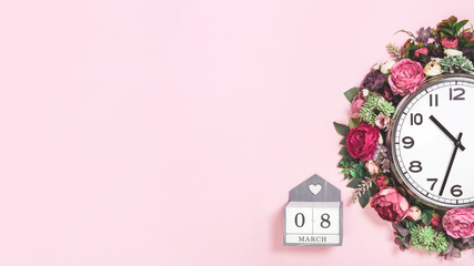 Part of big analogue plain wall clock in full bloom flowers on candy pink background. Close up with copy space banner. Daylight saving time. Spring or wedding. Womens day picnic banner