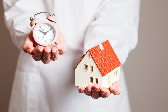 Woman holding alarm clock and mockup house