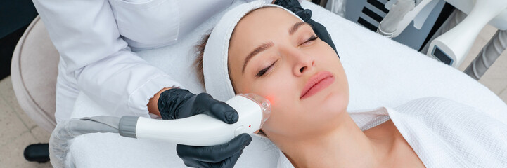 Young woman receiving laser treatment in cosmetology clinic Fotobehang