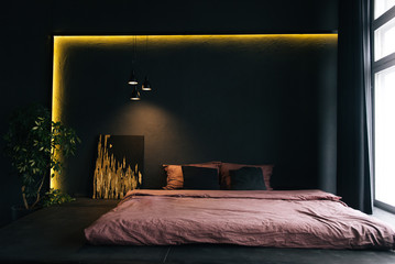 The interior of a modern apartment in black with yellow lighting. Beautiful interior decor