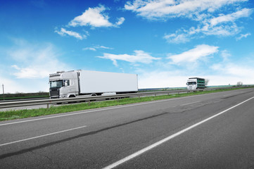 A big white truck and trailer with other truck on the countryside road against a blue sky with clouds Wall mural