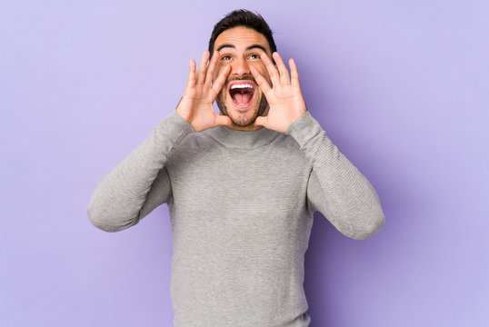 Young caucasian man isolated on purple background shouting excited to front.