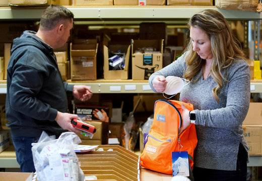 Kristen Curley (R), owner of Nitro-Pak, and an employee, put items into a backpack as part of personal protection and survival equipment kits ordered by customers preparing against novel coronavirus, at Nitro-Pak in Midway
