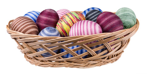Easter eggs decorated by cotton thread in wicker basket isolated on white background. Streaked egg shells wrapped by glued thin colored sewing yarn. Ornate decoration. Front view. Full depth of field.