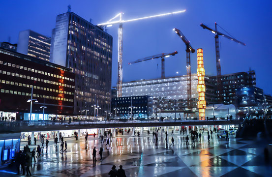Stocholm city in Sweden. Sergels plaza also called Plattan during nighttime in the Winter. Lots of people on their way. Big cranes building the new infrastructure of the capital.