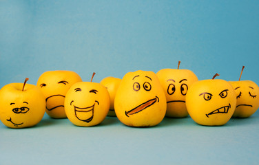 different emotions from joy to sadness and anger Face on an apple - abstract image of human emotions on blue background