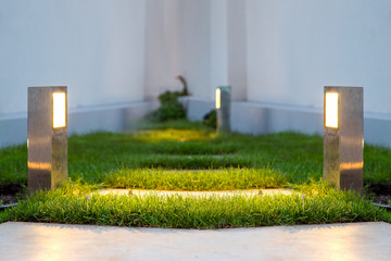 ground lantern lighting marble walkway in the evening backyard with a green lawn, closeup lamp illumination warm light marble pavement.