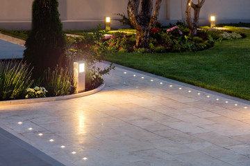 Wall Murals Dark grey marble tile playground in the night backyard of mansion with flowerbeds and lawn with ground lamp and lighting in the warm light at dusk in the evening.