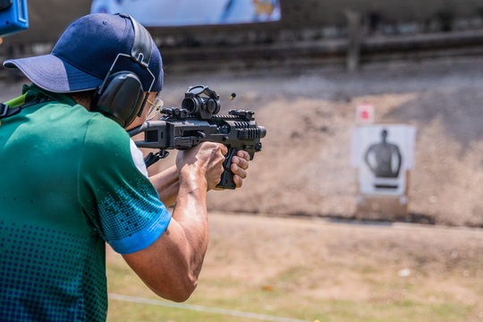 selective focus of man holding and fire sub machine gun to target in gun shooting competition