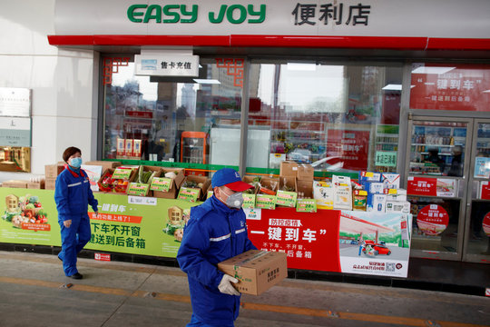 A pump attendant carries a box of groceriees into a car at a Sinopec gas station in Beijing where customers can buy supplies while they refuel