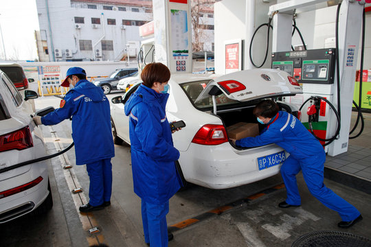 A pump attendant puts a box of groceriees into a car at a Sinopec gas station in Beijing where customers can buy supplies while they refuel