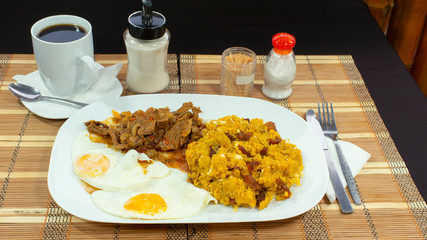 TIGRILLO is a typical dish consisting of ground green banana with cheese served in a green plate on a purple table accompanied with fried egg and meat and a cup of coffee