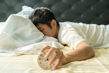 Asian man  wake up in the morning and hand reaching alarm clock Fotomurales