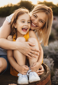 Caucasian girl sitting near her mother on a barrel while smiling and embracing each other during a sunny evening