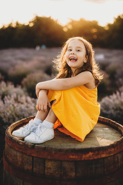 Caucasian small girl dressed in a yellow dress smiling happily while sitting on a barrel against a lavender field