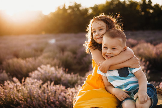 Careful sister embracing her small brother while posing against the sunshine with a lavender field on background