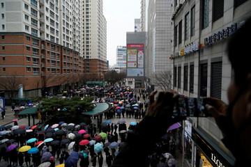 A man takes photographs of people waiting in a line to buy masks in front of a department store in Seoul