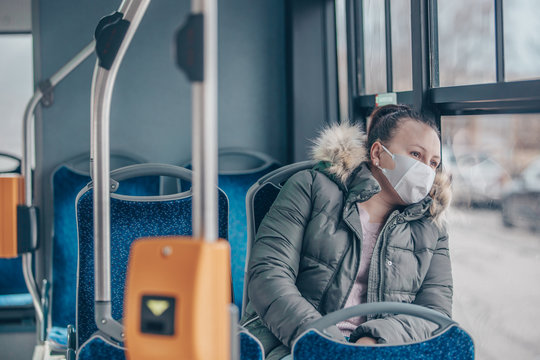 Coronavirus covid 2019 woman with respiratory mask traveling in the public transport by bus, transportation cocnept