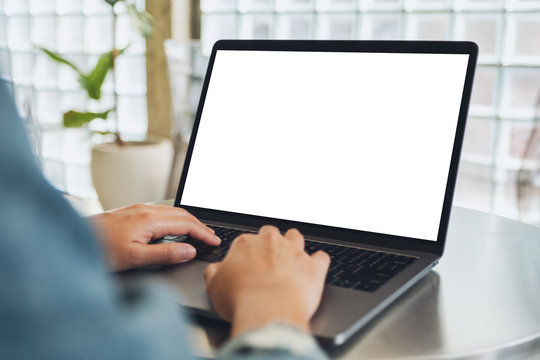 Mockup image of a woman using and typing on laptop computer with blank white desktop screen