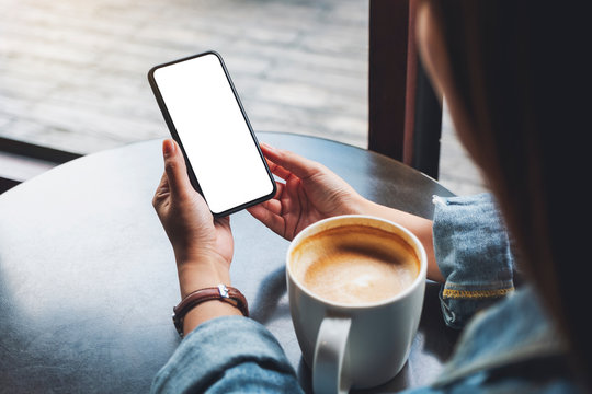 Mockup image of a woman holding black mobile phone with blank white screen with coffee cup on the table