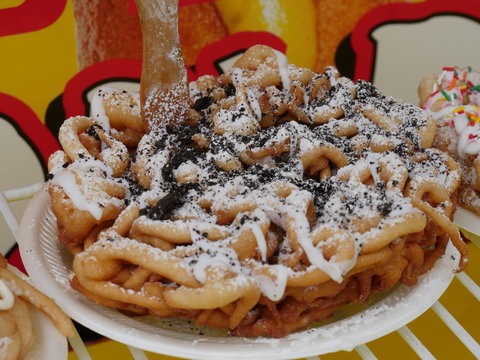 Close up of a chocolate caramel-flavored funnel cake with colored candy toppings