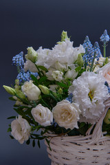 Foto op Canvas Lelie Bouquet. Composition of fresh, delicate flowers in a white basket against a dark background.