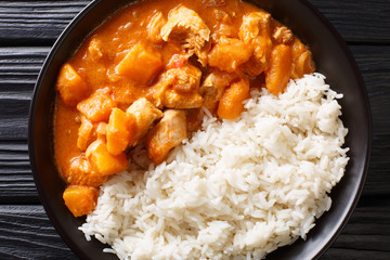 Fototapeta Domoda is the national dish of Gambia, a peanut stew made with meat pumpkin and served over fluffy rice close-up in a plate. Horizontal top view obraz