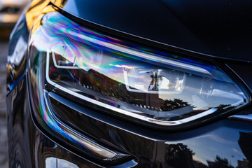 Close up photo of modern car, detail of headlight. Headlight car Projector LED of a modern luxury...