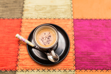 top view of espresso in a black coffee cup covered with aromatic cinnamon on multicolored background