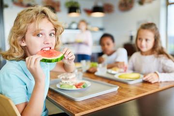 Junge in der Kantine isst eine Melone