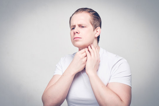 A man massages his neck while feeling for a furuncle near his neck. The concept of a weak immune system.