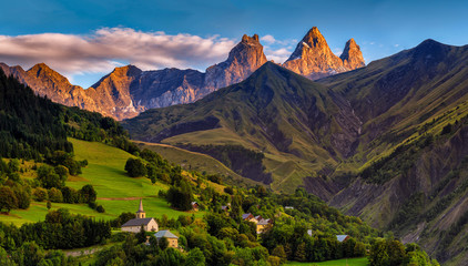 Photo sur Plexiglas Alpes church in a village in the french alps with mountains 3000 meters high. Green meadows in spring