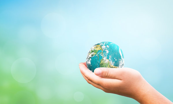 hand holding global over blurred  nature background