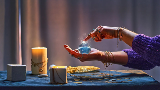 Witch woman with magic elixir potion bottle around candles and magical accessories during alchemy witchcraft