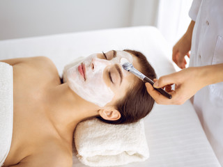 Printed kitchen splashbacks Spa Beautiful brunette woman enjoying applying cosmetic mask with closed eyes. Relaxing treatment in medicine and spa center concepts