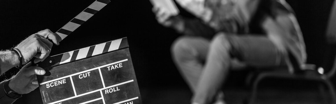 panoramic shot of actor with clapperboard in front, isolated on black, black and white