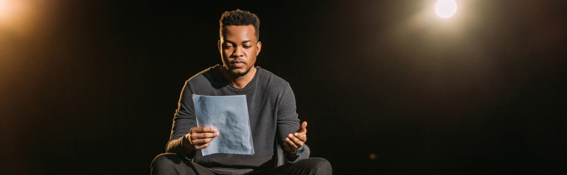 panoramic shot of african american actor holding scenario on stage during rehearse