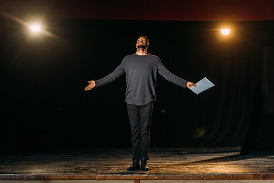 african american actor holding scenario and standing on stage during rehearse