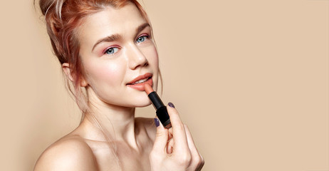 Portrait of gorgeous smiling woman holding rosy lipstick in hand. Model posing in studio and looking in camera gracefully. Beauty and cosmetics concept. Isolated on beige Wall mural