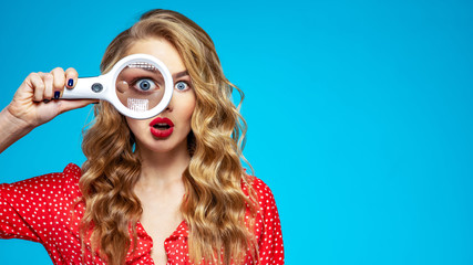 Surprised blonde holds a magnifying glass in front eye. Wonder young woman holds a magnifying glass in front of her eye. Funny girl with a bright smile and loupe. Eyesight care. Funny face of a girl Fotobehang