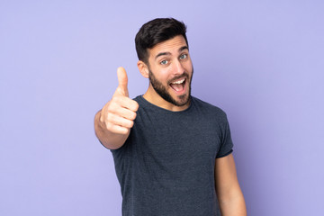 Caucasian handsome man with thumbs up because something good has happened over isolated purple background Wall mural