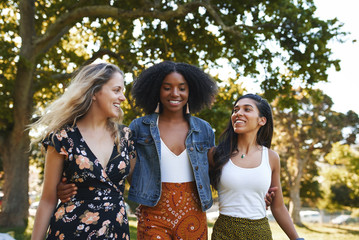 Group of smiling happy multiracial female friends walking together happily in the park on a sunny day