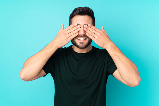 Caucasian handsome man isolated on blue background covering eyes by hands