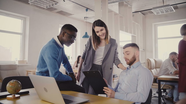 Caucasian female boss helping young multiethnic colleagues. Woman manager motivates employees in modern loft office 4K.